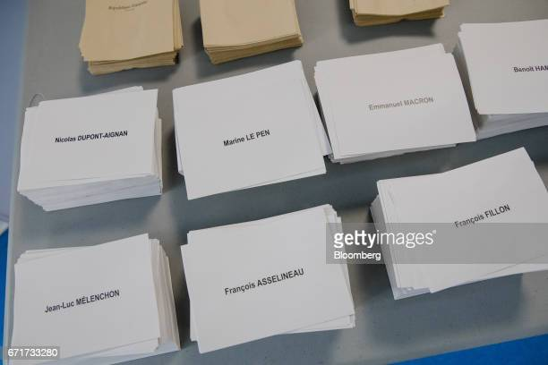 Voting papers marked with the names of presidential candidates sit in piles on a table at a polling station during the first round of the French...