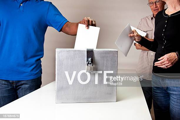 Voting. People in line casting vote. Ballot box.  Multi-ethnic group.
