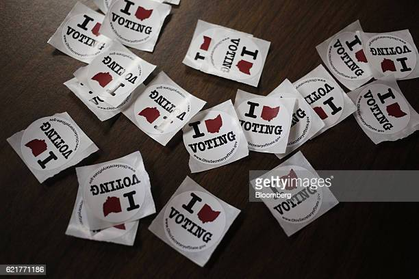 Voting stickers sit on a table at the United Auto Workers Local 1250 polling location in Brook Park Ohio US on Tuesday Nov 8 2016 The Justice...