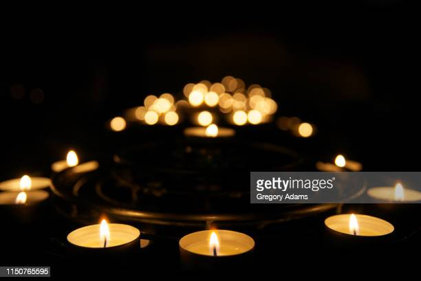 votive candles burning in the darkness - cero foto e immagini stock