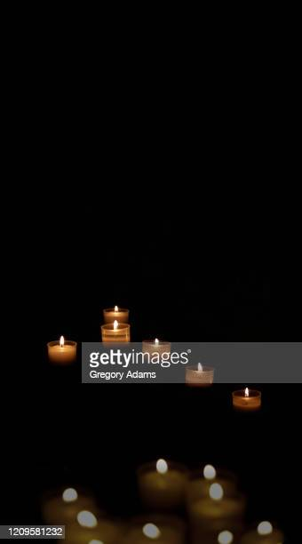 votive candles on a black background in a church in rome, italy - cero foto e immagini stock