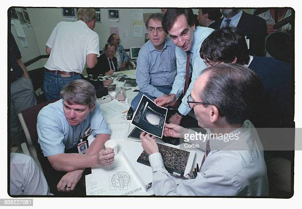 Voyager 2 scientists Carl Sagan and Ed Stone look at images that Voyager made of Neptune's moon Triton