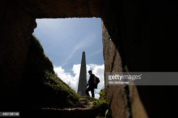 A vsitor pays his respects at the First Infantry Division memorial adjacent to a former German concrete bunker above Omaha Beach on the eve of the...