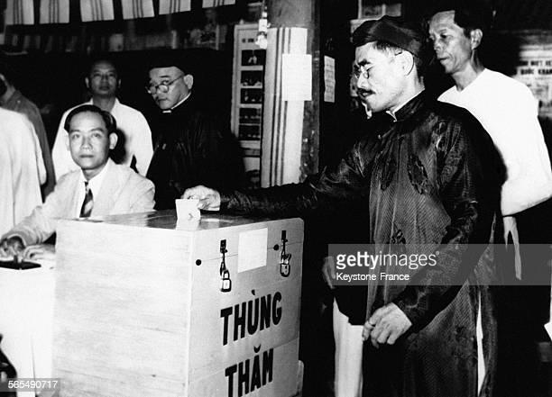 Vêtu d'un vêtement traditionnel un électeur dépose son bulletin de vote dans l'urne au Viêt Nam le 31 janvier 1953