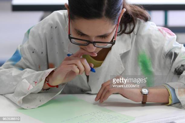 Vêtue de sa blouse blanche une lycéenne est en pleine réflexion penchée sur son brouillon lors dune épreuve de biologie du baccalauréat scientifique...