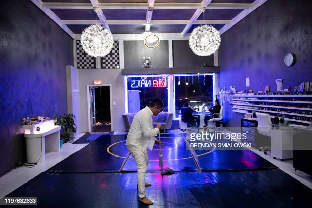 Vu Pham clean a wrestling mat at VIP Nails January 23 in Defiance, Ohio. Vu Pham, who's parents had him smuggled out of Viet Nam on a fishing boat in...