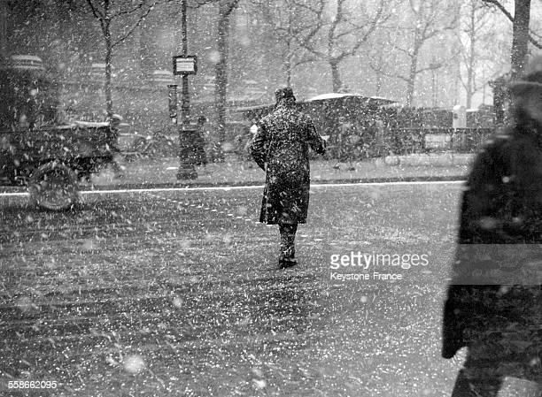 Vue de dos d'un homme qui traverse une rue alors que la neige tombe à gros flocons à Paris France