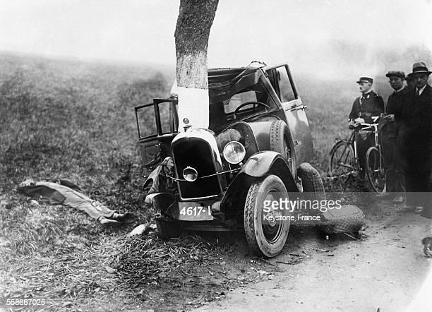 Vue de la voiture qui s'est écrasée contre l'arbre à gauche le cadavre git au sol près de Metz France le 10 novembre 1931