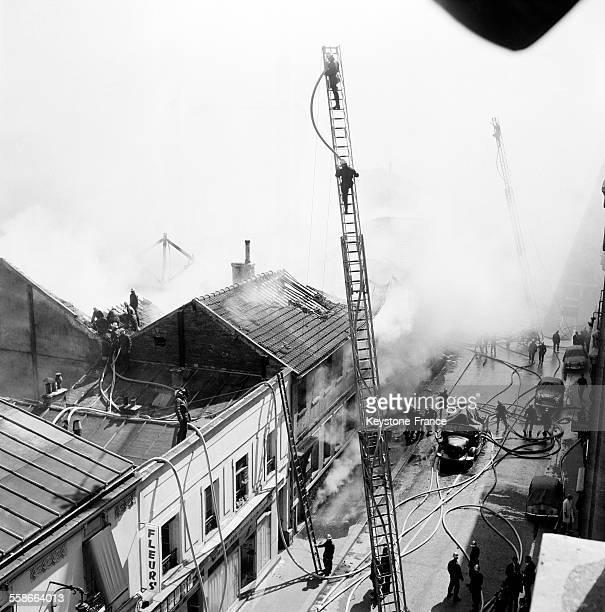Vue d'ensemble des dégâts matériels de cet incendie pendant que les pompiers luttent encore à Paris France le 2 juillet 1964
