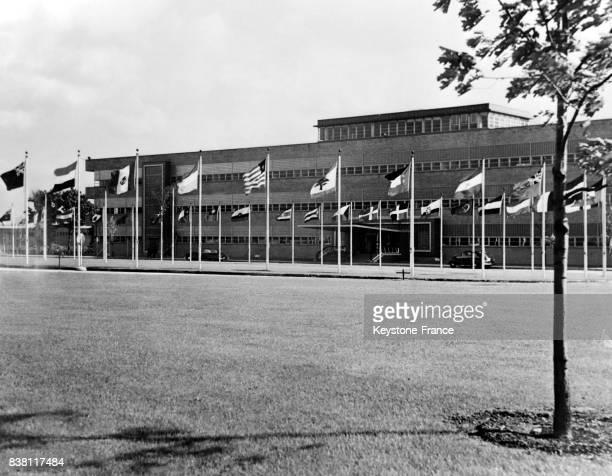 Vue extérieure du bâtiment dans lequel se tient la deuxième session de l'ONU les drapeaux de toutes les nations participantes sont plantés à Flushing...