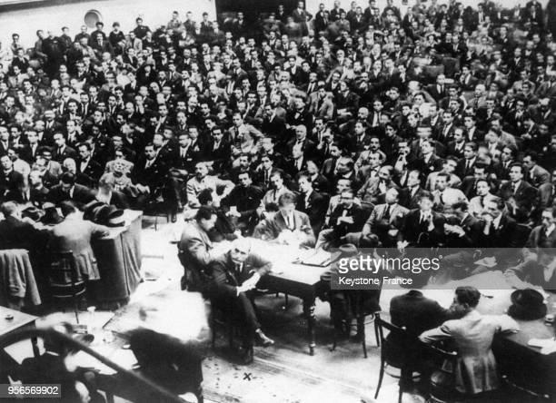 Vue générale de la salle du théâtre Auguste où se déroule le premier meeting fasciste Mussolini est assis à une table au centre le visage tourné vers...