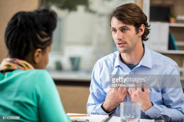 vulnerable man discusses something with therapist - vulnerability stock photos and pictures