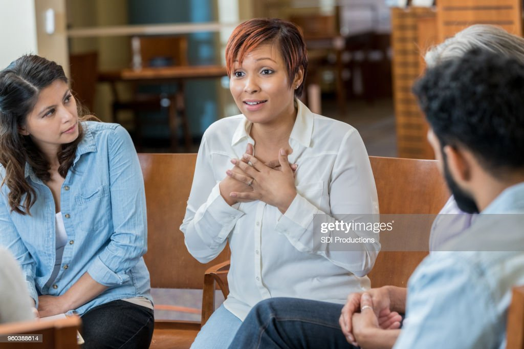 Vulnerable woman discusses something in support group : Stock Photo