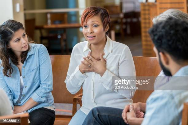 vulnerable woman discusses something in support group - vulnerability stock pictures, royalty-free photos & images