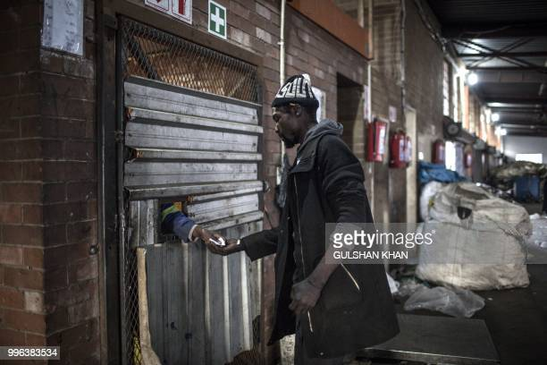TOPSHOT Vusi Matuna gets payed at Mudimu Recycling a buy back centre in Selby Johannesburg where reclaimers bring waste to be weighed and sold on...