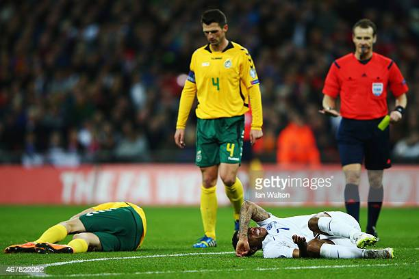 Vytautas Andriuskevicius of Lithuania and Raheem Sterling of England lie on the floor after a tackle during the EURO 2016 Qualifier match between...