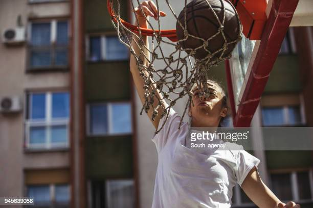 w9oman basketball player doing a slam dunk - shooting baskets stock pictures, royalty-free photos & images