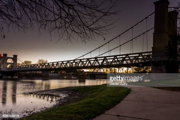 waco, texas feb 24, 2017:  the waco suspension bridge after sunset with lights along the cables illuminated, was taken from the northern bank of the brazos river. - waco stock pictures, royalty-free photos & images