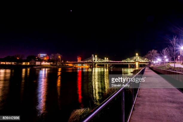 waco, texas february 24, 2017:  lights from the interstate 35 bridge reflecting off the river as seen from the bank of the brazos river. - waco foto e immagini stock