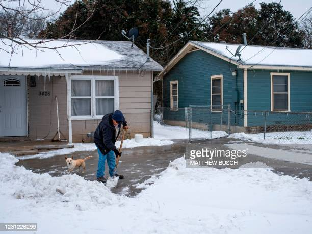 Waco, Texas, resident clears snow from his driveway alongside his dog on February 17, 2021 as severe winter weather conditions over the last few days...