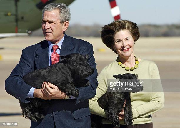 US President George W Bush carries his dog Barney as Fist Lady Laura Bush holds Miss Beazley after stepping off Air Force One 26 December 2005 upon...