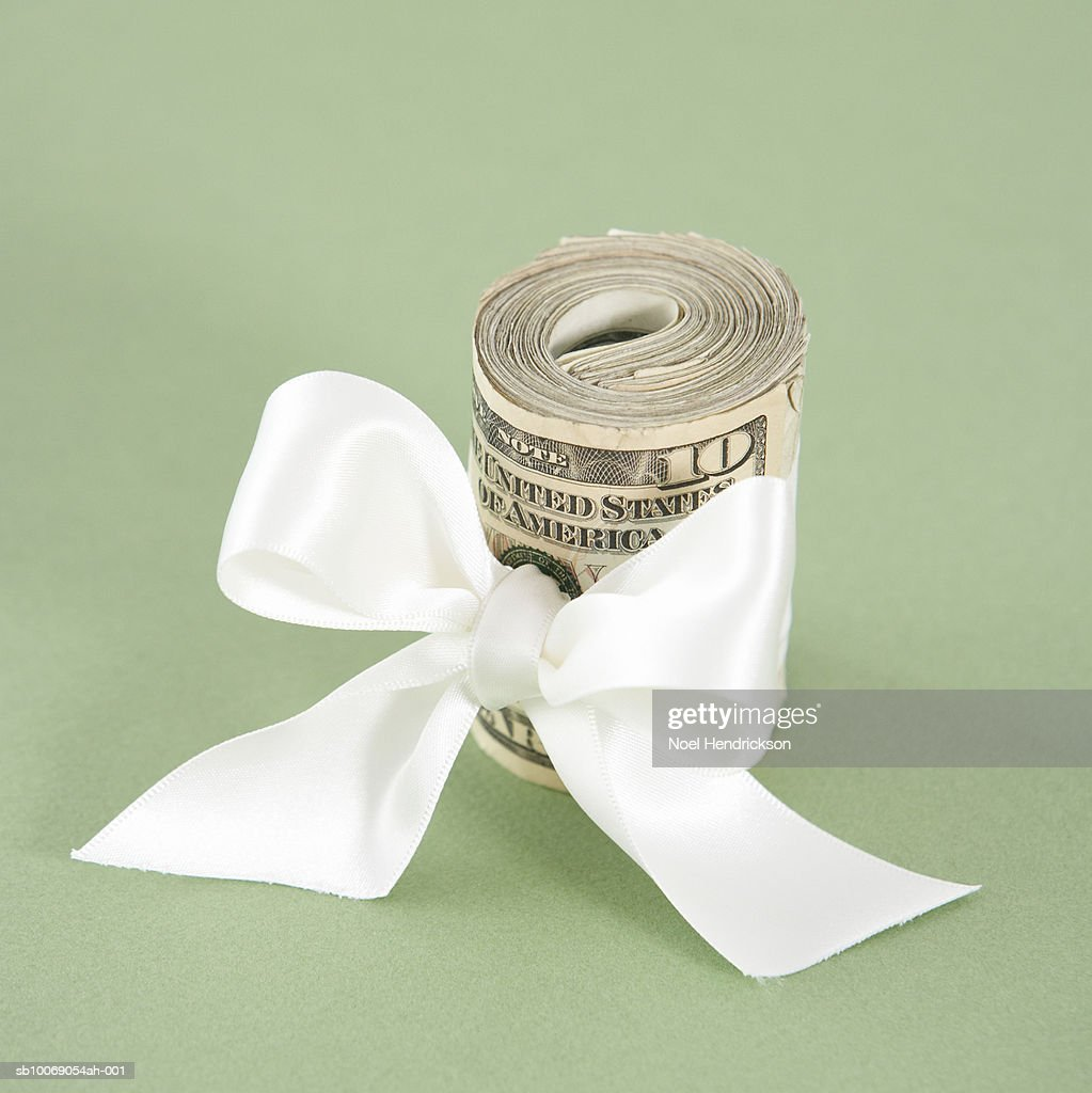 Wad of money tied with ribbon : Stockfoto