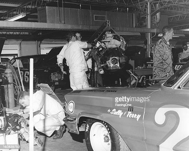Waddell Wilson is shown inspecting engine parts prior to changing an engine in the Fireball Roberts HolmanMoody Ford in the garage area before a...