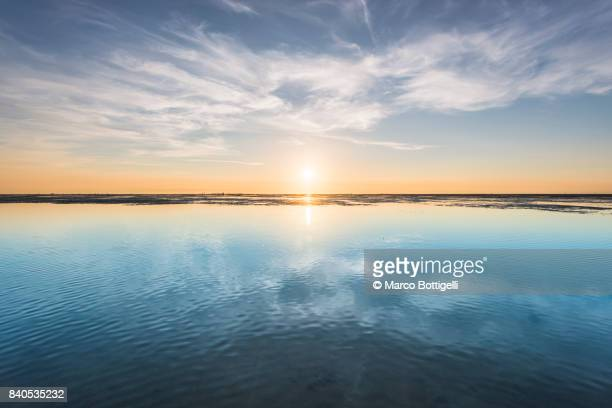 wadden sea at sunset. cuxhaven, germany - horizon stockfoto's en -beelden