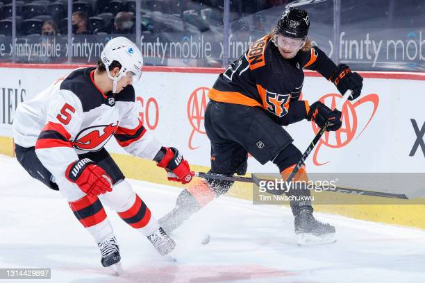 Wade Allison of the Philadelphia Flyers passes past Connor Carrick of the New Jersey Devils during the third period at Wells Fargo Center on April...