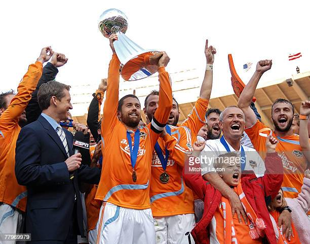 Wade Barrett of the Houston Dynamo holds up the trophy in celebration with his team after defeating the New England Revolution by a score of 21 to...