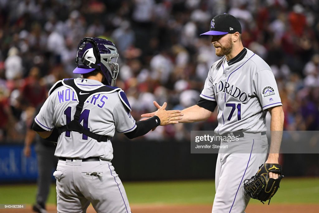 Wade Davis #71 and Tony Wolters #14 of the Colorado Rockies celebrate after closing out the MLB game against the Arizona Diamondbacks at Chase Field on March 31, 2018 in Phoenix, Arizona.