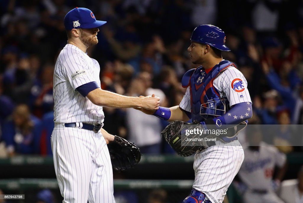 Wade Davis #71 and Willson Contreras #40 of the Chicago Cubs celebrate after beating the Los Angeles Dodgers 3-2 during game four of the National League Championship Series at Wrigley Field on October 18, 2017 in Chicago, Illinois.