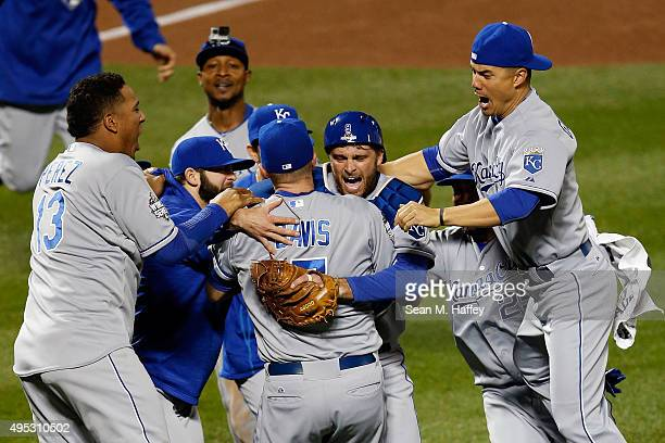 Wade Davis of the Kansas City Royals and Drew Butera of the Kansas City Royals celebrate with teammates after defeating the New York Mets to win Game...