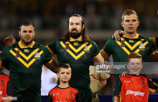 Wade Graham Aaron Woods and Tom Trbojevic of Australia sing the national anthem during the 2017 Rugby League World Cup match between Australian...