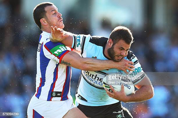Wade Graham of the Sharks is tackled during the round 20 NRL match between the Cronulla Sharks and the Newcastle Knights at Southern Cross Group...
