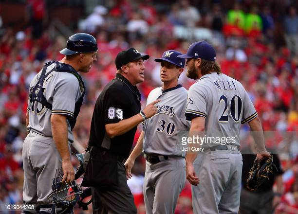 Wade Miley manager Craig Counsell and Erik Kratz of the Milwaukee Brewers argue with umpire Cory Blaser after both benches were warned during the...