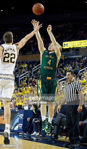 Wade Schetter of the Northern Michigan Wildcats takes a shot against Duncan Robinson of the Michigan Wolverines during the second half at Crisler...
