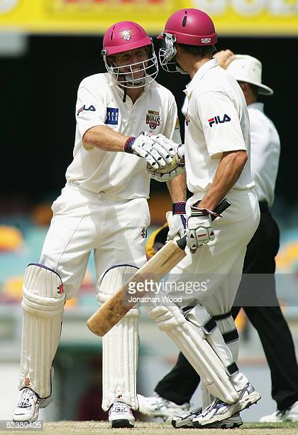 Wade Seccombe of the Bulls celebrates 50 runs with team mate Mitchell Johnson during day four of the Pura Cup match between the Queensland Bulls and...
