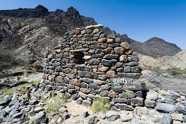 The ruins of a handmade stone house in an arid desert valley.