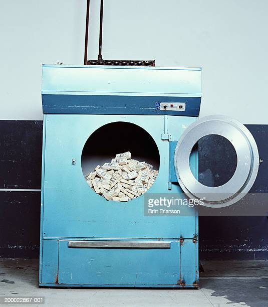 wads of bank notes in industrial washing machine - money laundering stock photos and pictures