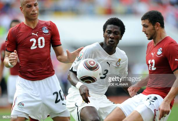 Wael Gomaa and Hossam Ghali of Egypt vie with Asamoah Gyan of Ghana during the final match between Egypt and Ghana during African Cup of Nations...