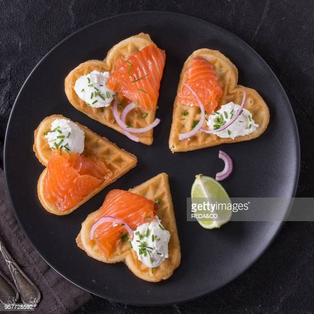 Wafers as heart shape with salted salmon, onion, chive, lime and ricotta cheese on black plate with vintage cutlery and textile napkin over black...