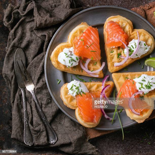 Wafers as heart shape with salted salmon red onion chive lime and ricotta cheese on metal plate with vintage cutlery and sackcloth rag over dark...
