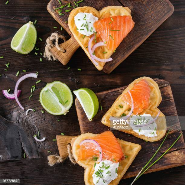 Wafers as heart shape with salted salmon red onion chive lime and ricotta cheese on small wooden cutting boards over dark wood background Top view...