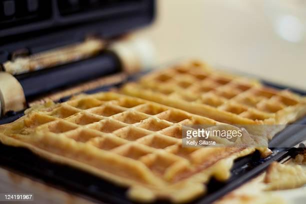 Waffle iron with fresh golden waffles