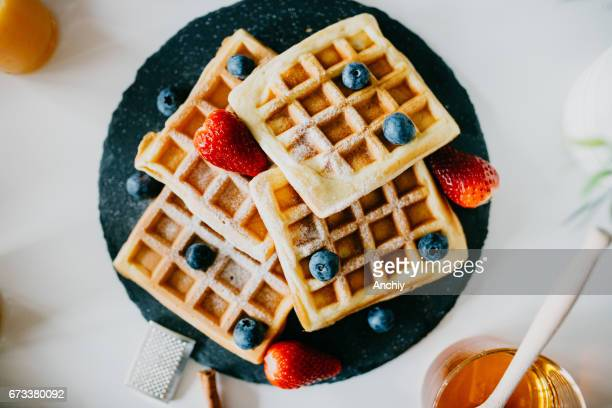 Waffles with blueberries, strawberries and powdered sugar