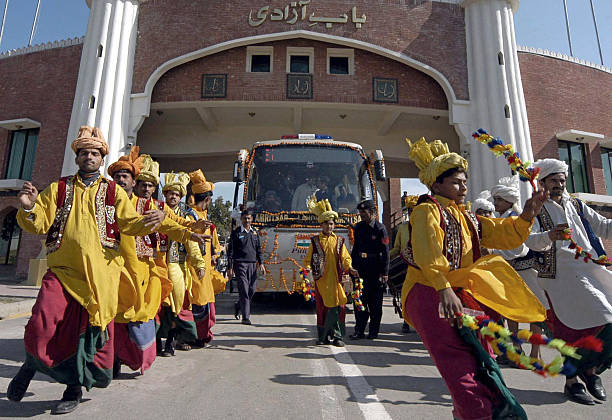 Pakistani folk dancers perform a traditional Bhangra dance upon arrival the of AmritsarLahore bus at the Wagah Border post 24 January 2006 The...