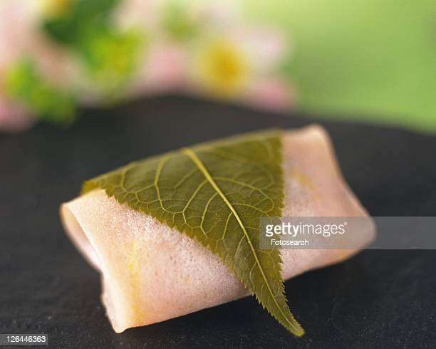 Wagashi called sakuramochi on tray, flower visible in background, high angle view, Differential Focus, close up