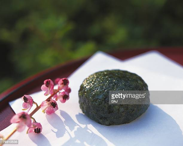 wagashi called yomogimochi, japanese sweet and flower on japanese paper, differential focus - japanese mugwort stock pictures, royalty-free photos & images