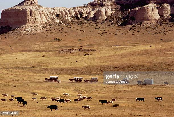 Wagon Train Crossing Prairie Lined With Cliffs